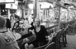 Image shows a woman sitting at a bar smiling.