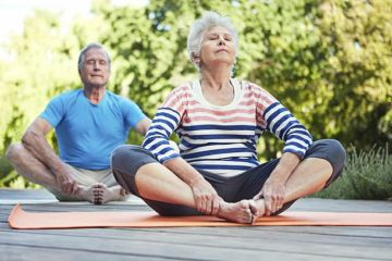 Image shows an older lady and man in a yoga pose.