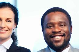 Image shows a smiling people in suits.