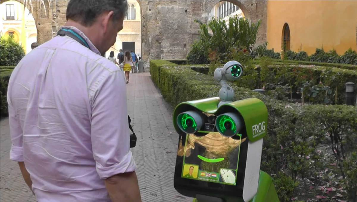 Image shows a man interacting with the FROG robot.