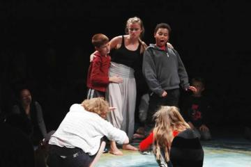 Image shows children performing a scene on a stage.
