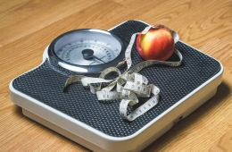 Image shows a scale, tape measure and apple.