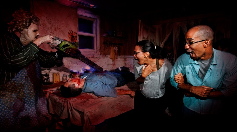 Leatherface carves a victim in Texas Chain Saw Masacre maze at Halloween Horror Nights 2012