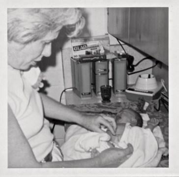 Grandma and newborn Jill at the kitchen sink for first bath.