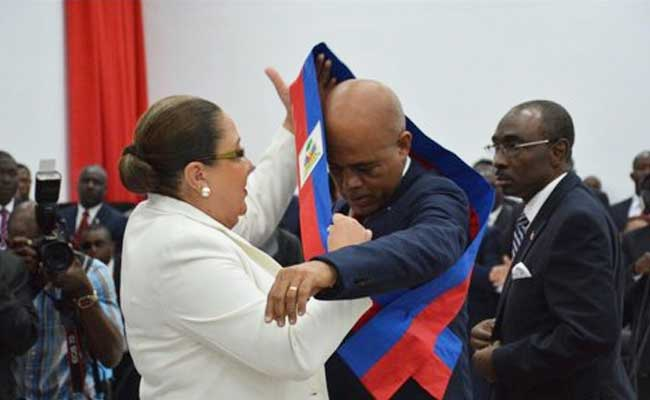 Remise de l'écharpe présidentielle au président de l'Assemblée Nationale.