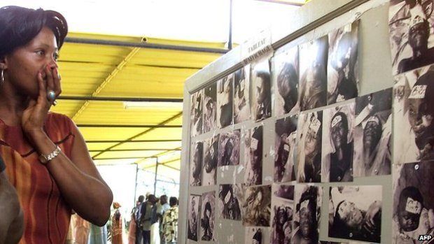 A woman looks at photos of people who died in the Joola ferry disaster - photo taken on 29 September 2002