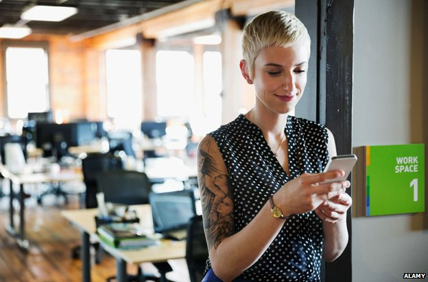 A woman on her phone in an office with a large tattoo on her upper arm