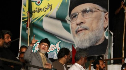 Pakistan's fiery cleric Tahir-ul-Qadri, second left, gestures while delivering his speech during a protest in Islamabad, Pakistan,