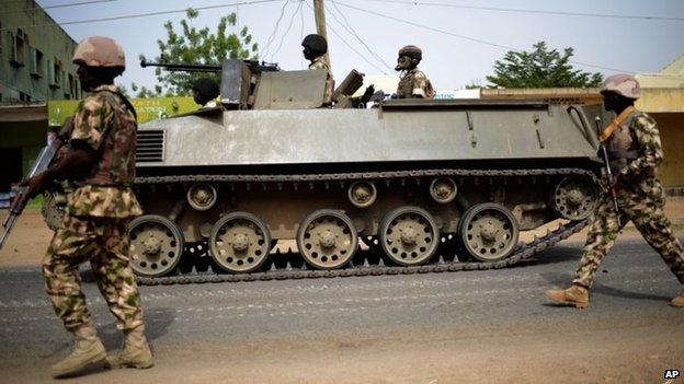 In this photo taken Monday March 9, 2015, Nigerian troops patrol in the north-eastern Nigerian city of Mubi, some 20 kms (14 miles) west of the Cameroon border. Nigerian troops recaptured Mubi from Boko Haram militants in February 2015.