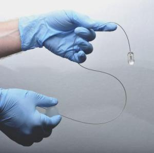 By manipulating the plastic ball attached to the flexible tether (lower, right hand) the system operator can control the position of the endomicroscopy capsule in a patient's esophagus. Credit: Michalina Gora, Ph.D., and Kevin Gallagher, Wellman Center for Photomedicine, Massachusetts General Hospital.