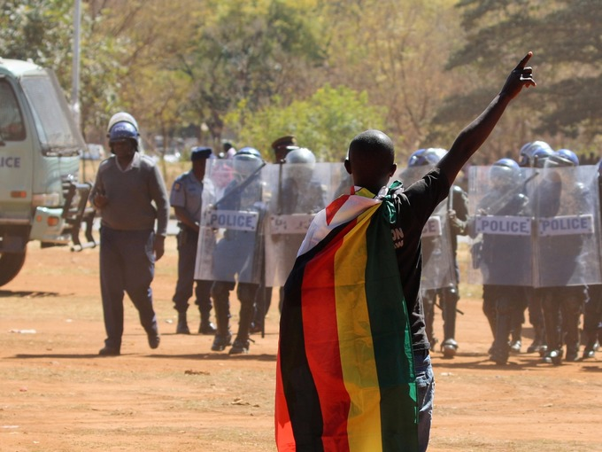 An opposition supporter stood defiant against armed officers.