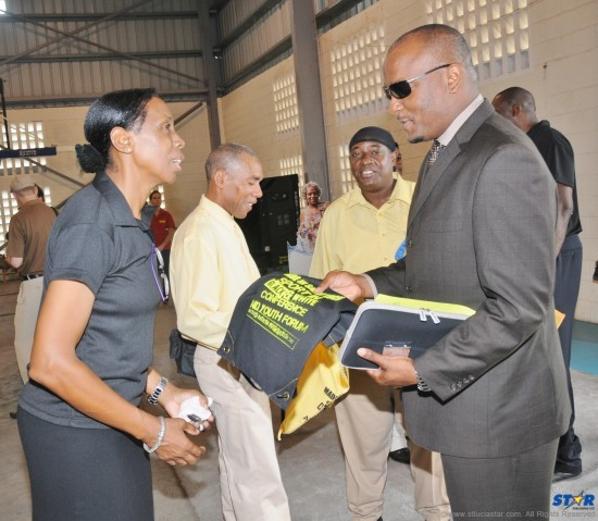 Minister of Youth Development and Sports, Shawn Edward, greeted by Sacred Sports Foundation Executive, Nova Alexander, at Monday's official opening of the Sport in Black and White Conference and Youth Forum.