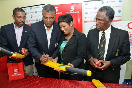 Dave Cameron looks on as WICB President Michael Muirhead signs a kiddy cricket bat to mark the new contract signing. Also observing the proceedings is Linval Wright, President  of the Jamaica Cricket Association.