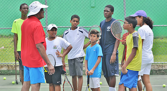 Participants of the Tiger Tennis/SLTAI Summer Camp listen attentively as Coach Earl Blanchard instructs them on the nuances of the game.