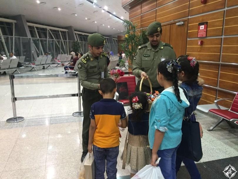جوازات مطار الأمير سلطان بن عبدالعزيز يوزع الحلوى و الورود على المسافرين 2