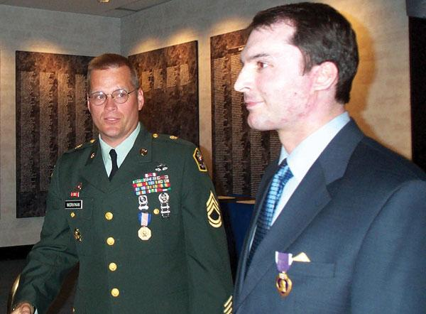 Author receiving the Purple Heart in a April 26, 2002 ceremony with U.S. Army Sgt. 1st Class Steve Workman. Sgt. 1st Class Workman transported the author to one of the first ambulances that arrived on the scene after the crash. U.S. Army photo