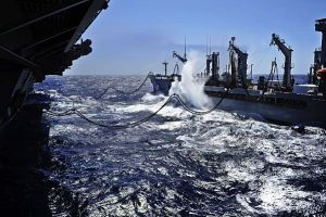 A wave strikes the side of to the Military Sealift Command fleet replenishment oiler USNS Henry J. Kaiser (T-AO 187) as it conducts a replenishment at sea with the aircraft carrier USS Nimitz (CVN 68) on July,7.[U.S. Navy Photo]