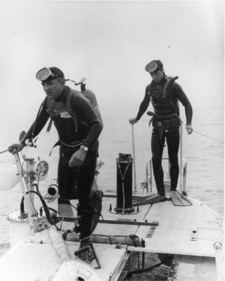 John Houchen, left, and N.D. Smith, SOS2(SS), on right, divers attached to the Trieste, going overboard to inspect the hull and attach equipment. Naval Institute Archives