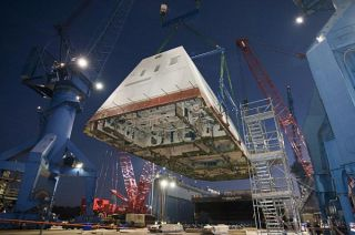 The deckhouse of the future destroyer USS Zumwalt (DDG 1000) is craned toward the deck of the ship to be integrated with the ship's hull at General Dynamics Bath Iron Works. US Navy Photo