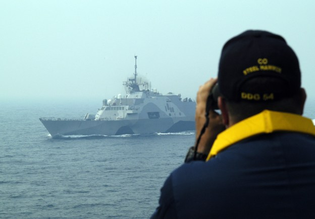 Cmdr. Joe Femino, commanding officer of USS Curtis Wilbur (DDG 54) watches USS Freedom (LCS 1) through a pair of binoculars on June 20. US Navy Photo
