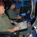 Lt. Cmdr. Jeremy DeYoung and Naval Aircrewman 1st Class David Berber, both reservists attached to Helicopter Anti-Submarine Squadron Light (HSL) 60, demonstrate the MQ-8B Fire Scout flight simulator in 2012. US Navy Photo