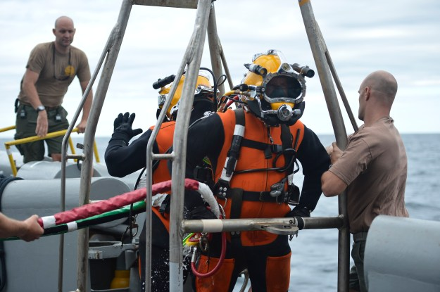 Divers, assigned to Mobile Diving Salvage Unit 2, Company 2-4, wait on the diving stage to be lowered into the water during air surface supplied diving operations off the coast of Virginia on Aug. 16, 2013. US Navy Photo