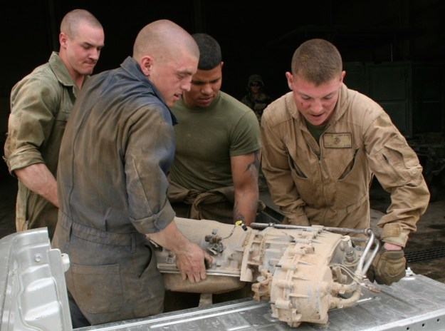 Marines with Combat Logistics Company, Combat Logistics Battalion 7 work together to put a transmission in the back of one of their vehicles aboard Camp Shorabak, Helmand province, Afghanistan on March 12, 2014. US Marine Corps Photo