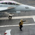 A sailor directs an EA-18G Growler from the Cougars of Electronic Attack Squadron (VAQ) 139 on the flight deck of the aircraft carrier USS Carl Vinson (CVN-70) on May 21, 2014 US Navy Photo