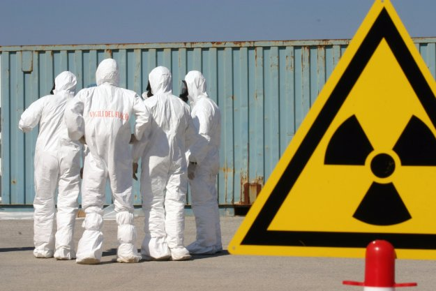 Italian firefighters dressed in chemical, biological, radiological (CBR) suits set up a perimeter of signs around a container suspected of carrying weapons of mass destruction (WMD) during a US led exercise in 2004. US Navy Photo