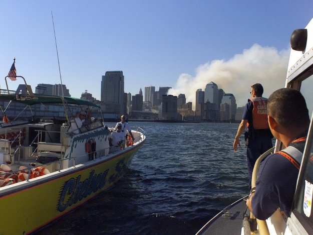 A Coast Guard boarding team aboard a 41-footer looks over a privately owned vessel in New York Harbor as the World Trade Center site burns in the background. US Coast Guard Photo