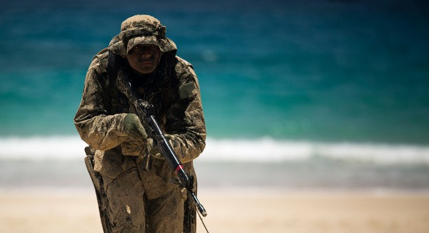 Japan Ground Self-Defense Force (JGSDF) soldier advances positions while his squad member provides cover during an amphibious assault at Pyramid Rock Beach on July 1, 2014. US Navy Photo