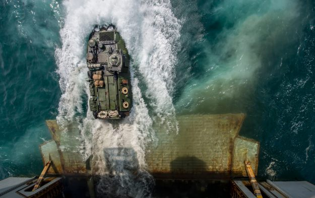 Marines aboard an amphibious assault vehicle (AAV) exit the well deck of the amphibious assault ship USS Bataan (LHD-5) on Aug. 24, 2014. US Navy Photo