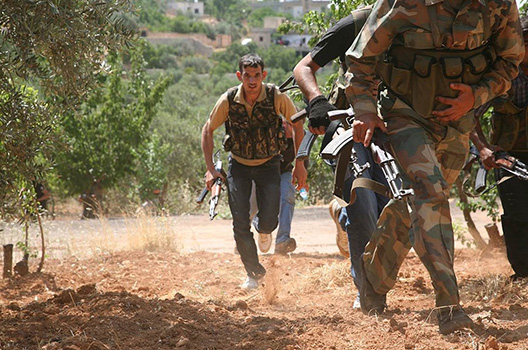 """Justice Brigade"" run through an olive grove to avoid Syrian Army snipers as they travel between villages on foot in the northwestern Jabal al-Zawiya area. Freedom House Photo via The Atlantic Council"