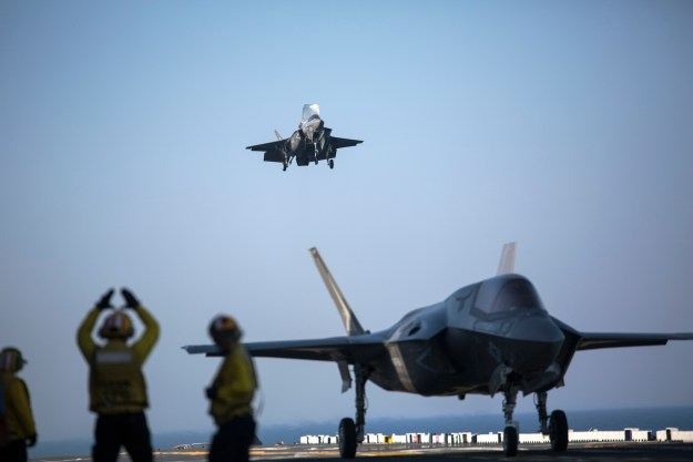 A sailor aboard the USS Wasp (LHD-1) signals to the pilot of an F-35B Lightning II Joint Strike Fighter to land as it arrives for the first phase of operational testing, May 18, 2015. US Marine Corps photo.