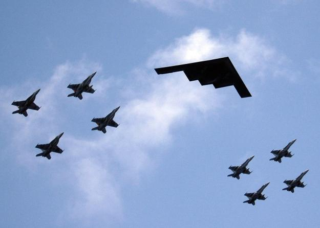A B-2 Stealth Bomber from Whiteman AFB in Missouri leads an aerial flight formation with F-18 Hornets from the during exercise Valiant Shield 2006. US Navy Photo