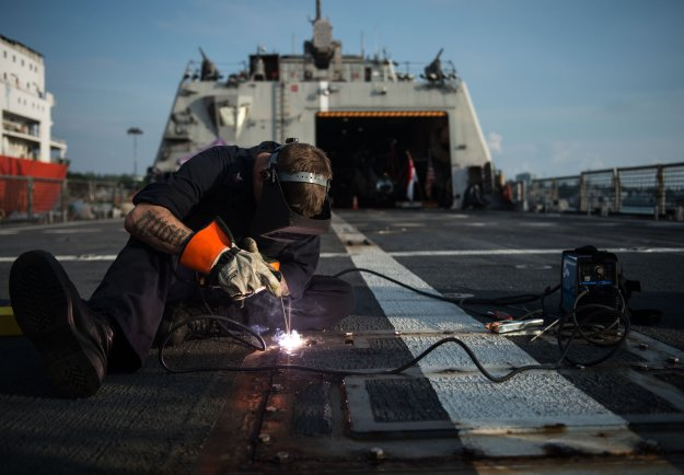 A sailor secures a bolt in place for the retractable bit for towing aboard USS Fort Worth (LCS-3). US Navy Photo
