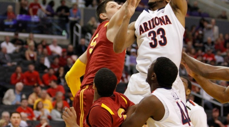 Arizona men's basketball player Jesse Perry (33) goes up and over USC's Nikola Vucevic to score basket in the Pacific Life Pac-10 Conference Tournament semifinals./Photo Credit: Bryan Corvarrubias/news4usonline.com