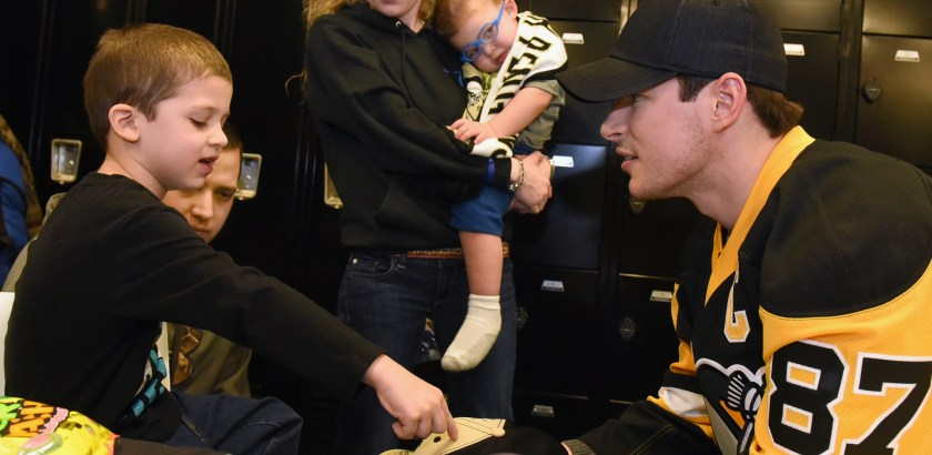 Bob Donaldson/Post-Gazette. 011916.  Pens Party. Standalone. Local. Justin Hudson, 6, shows Penguins captain Sidney Crosby where to sign his hat, as dad Justin, mom Kelsey, and brother Wyatt, 2, look on. They are from Crafton. They were attending the team's 29th annual Children's Practice and Party at the UPMC Lemieux Sports Complex Wednesday. Families attended the morning practice before greeting players at the party afterwards. Families from the Make-a-Wish Foundation, The Children's Institure and Children's Home of Pittsburgh attended. Writer: Standalone. Story Slug: not available