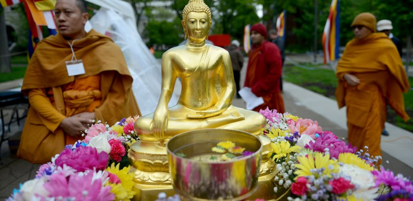 Michael Henninger/Post-Gazette 20160515MWHbuddhist Local A group of Buddhist monks gather around a Buddha statue before marching with it to the Allegheny River during Vesak, an annual celebration of the Buddha, held on Pittsburgh's North Shore on Sunday, May 15, 2016.