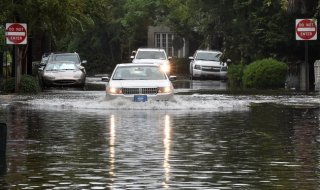 A car drives down a flooded street in Charleston, South Carolina on October 4, 2015. Relentless rain left large areas of the US southeast under water and forecasters warned that more heavy downpours could trigger historic flooding in the crucial next 24 hours. The states of North and South Carolina have been particularly hard hit, but the driving rain in recent days has spared almost none of the US East Coast and forecasters say the worst is not over quite yet. News reports blamed the wild weather on four deaths in the United States since Thursday, all in the Carolinas. AFP PHOTO/MLADEN ANTONOV        (Photo credit should read MLADEN ANTONOV/AFP/Getty Images)