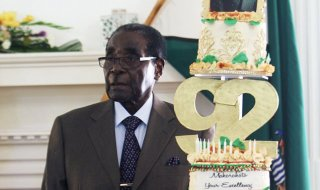 Zimbabwean President Robert Mugabe stands next to his Birthday cake at State House in Harare, Monday, Feb. 22, 2016. Office staff in the President's office organized a surprise birthday celebration ahead of  bigger birthday celebration set for Saturday in the southern town of Masvingo. Mugabe, the world's oldest leader, turned 92 Sunday with no plans to step down as  feuding  over his successors threatens to tear his ruling ZANU-PF party apart. (AP Photo/Tsvangirayi Mukwazhi)