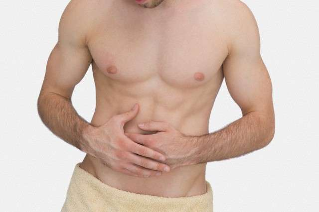 Midsection of man with stomach ache --- Image by © Wavebreak Media Ltd./Corbis