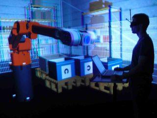 Im Virtual-Reality-Labor des Instituts für Arbeitsschutz in Sankt Augustin: Der Roboter und die Arbeitsumgebung werden täuschend echt dreidimensional auf einem Großbildschirm projiziert. Der Proband steht davor am Laptop und erteilt damit Befehle. Foto: Birgit Naber/IFA