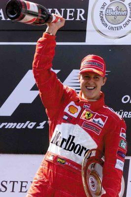 Mit der Trophäe unter dem Arm und einer großen Champagnerflasche jubelt der deutsche Formel-1-Pilot Michael Schumacher (Ferrari) am 24.06.2001 auf dem Podium bei der Siegerehrung über seinem Sieg im Rennen um den Großen Preis von Europa auf dem Nürburgring, dem neunten Lauf zur Formel-1-Weltmeisterschaft 2001. Der Weltmeister holt sich den fünften Saisonsieg und damit den insgesamt 49. Grand-Prix-Erfolg. © ADAC