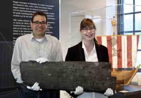 """Dr. Arnulf Siebeneicker und Linda Wilken mit einer originalen Planke der """"Bremer Kogge"""" aus dem 14. Jahrhundert. Foto: LWL/Holtappels"""