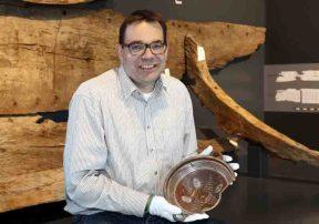 Museumsleiter Dr. Arnulf Siebeneicker präsentiert einen Teller, der vor über 200 Jahren mit zwei Lastkähnen auf den Grund der Weser sank. Foto: LWL/Holtappels