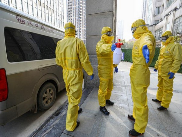Funeral parlour staff members in protective suits help a colleague with disinfection after they transferred a body at a hospital, following the outbreak of a new coronavirus in Wuhan, Hubei province, China January 30, 2020. Picture taken January 30, 2020. China Daily via REUTERS ATTENTION EDITORS - THIS IMAGE WAS PROVIDED BY A THIRD PARTY. CHINA OUT.