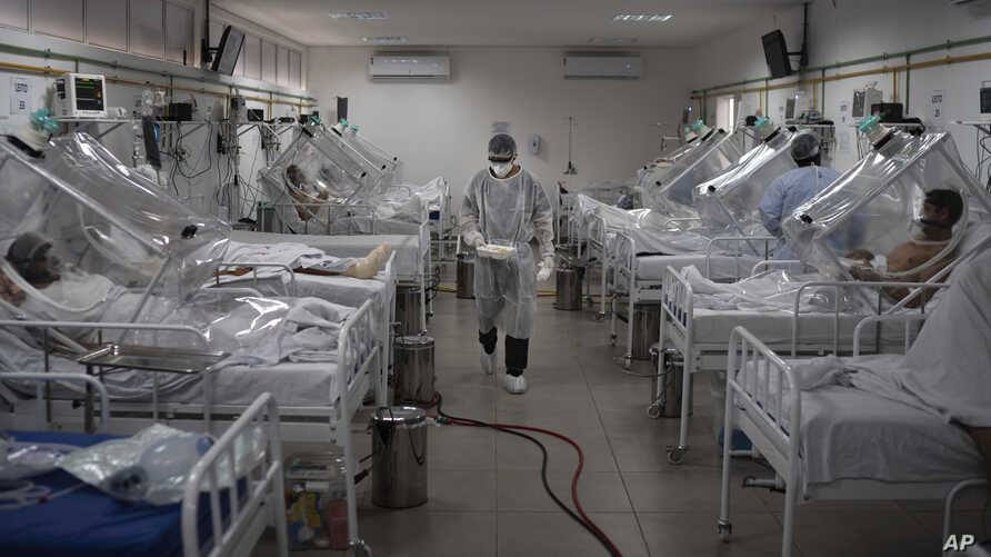 COVID-19 patients are treated inside a non-invasive ventilation system named the 'Vanessa Capsule' at the municipal field hospital Gilberto Novaes in Manaus, Brazil, Monday, May 18, 2020. The field hospital set up inside a school currently has nearly 150 beds and is operating near its limit as it treats patients both from the capital and from rural areas of the Amazon state. (AP Photo/Felipe Dana)
