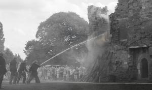 Firemen direct water to the fire - John Lee