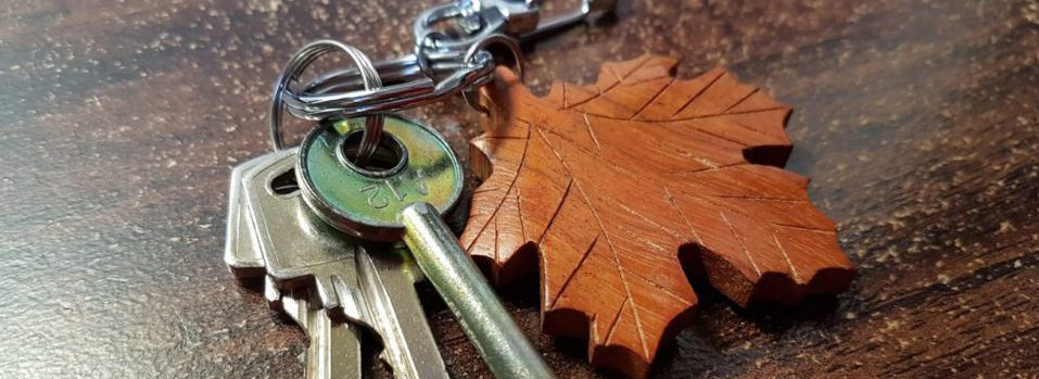 Brass keys on a key chain with a wooden maple leaf.